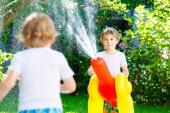 Fotografie Zwei Kinder kleine Jungs spielen mit einem Gartenschlauch Wasser sprinkler