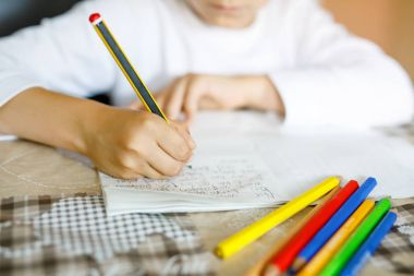 Child doing homework and writing story essay. Elementary or primary class