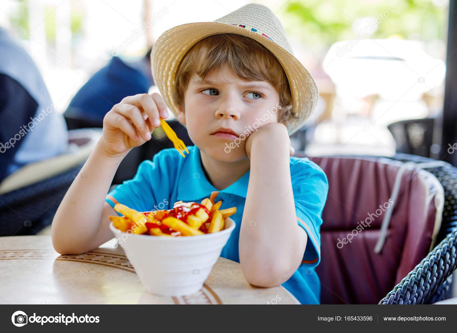 Süße gesunde Vorschule Kind junge isst Kartoffeln Pommes Frites mit ...