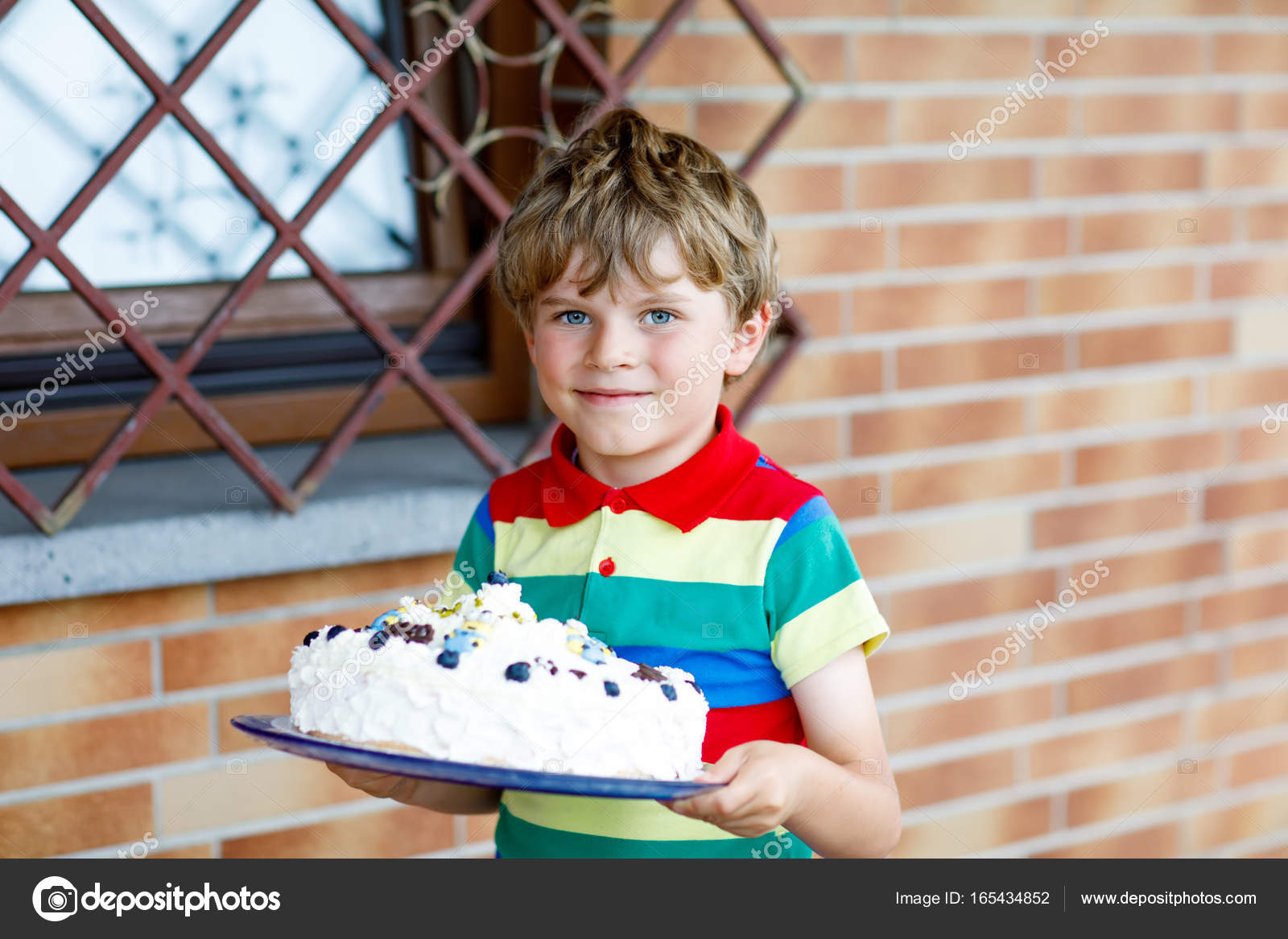 Cute blond kid boy holding big birthday cake Happy smiling child