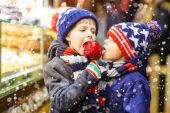 Zwei kleine Jungen essen Zuckerapfelbonbons am Stand auf dem Weihnachtsmarkt