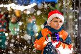 Kleiner Junge mit heißer Schokolade auf dem Weihnachtsmarkt