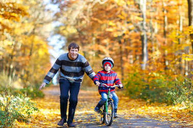 Little kid boy and his father in autumn park with a bicycle. Dad teaching his son biking