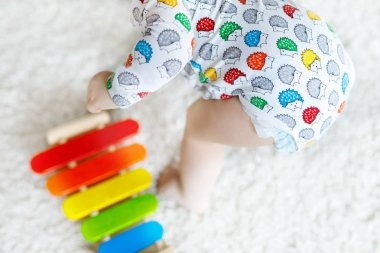 Adorable cute beautiful little baby girl playing with educational wooden toys at home or nursery. Toddler with colorful music toy