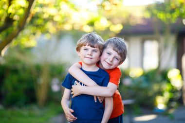 Two little active school kids boys, twins and siblings hugging on summer day