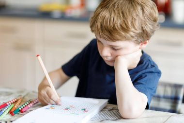 Tired kid boy at home making homework writing letters with colorful pens