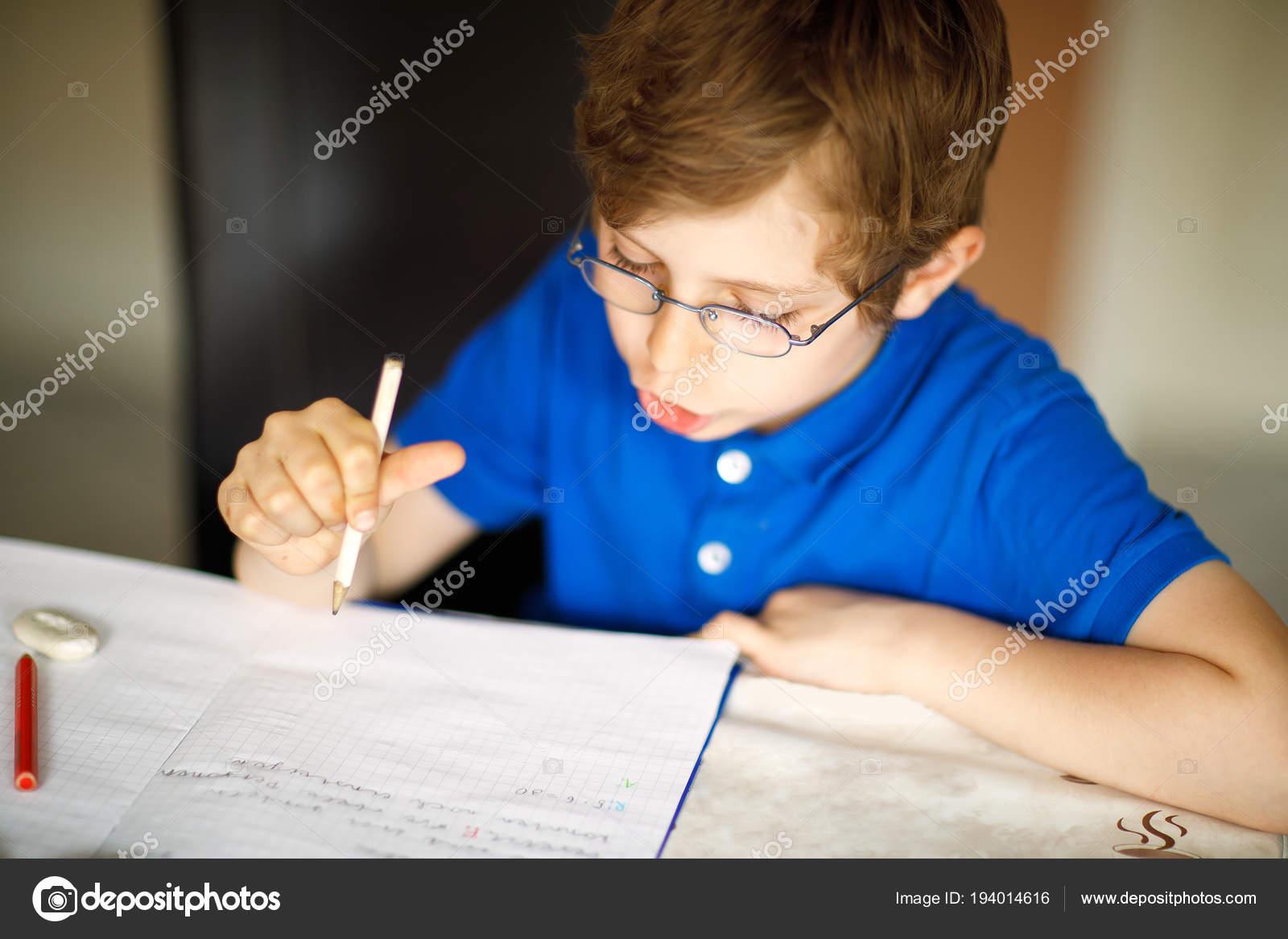 0cbf4f27935 Cute little kid boy with glasses at home making homework