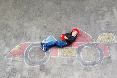 Adorable little kid boy drawing with colorful chalks race car picture on asphalt.
