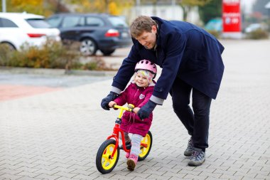 Cute little toddler girl in safety helmet riding on run balance bike. Middle-aged father teaching happy healthy lovely baby child daughter having fun with learning bicycle. Active family outdoors.