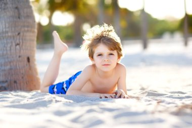 Blond little kid boy having fun on Miami beach, Key Biscayne. Happy healthy cute child playing with sand and running near ocean. Palms, security house and white sand. With sunny warm bright light