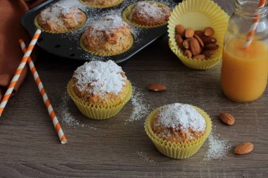 Fresh homemade orange muffin on wooden table background. Mini cake with nut flour. Healthy bakery food.