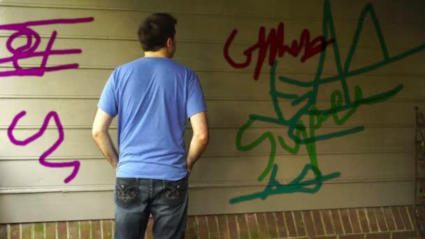 Člověk při pohledu na graffiti mimo budovu