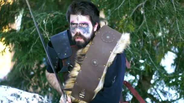 Viking muž s mečem na sněhu