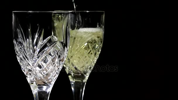 Pouring White Wine Into Two Crystal Wine Glasses