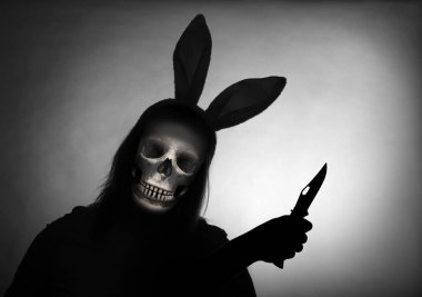 Silhouette of spooky robber or grim reapper with knife in rabbit costume.  Violence and criminality concept. A bloody Easter in the slum.