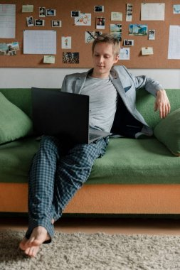 The boss in a jacket is sitting on the couch and holding a meeting on a laptop, sprawled on the couch