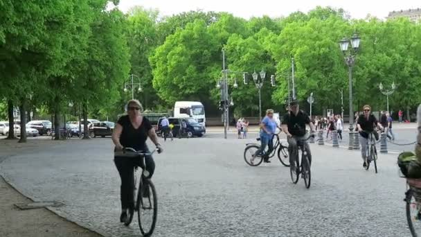 People riding by bike through the city of berlin. in background the reichstag and Brandenburger tor.