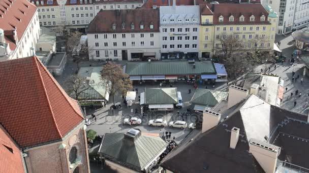 Luftaufnahme von St. Peter-Kirche. Menschen zu Fuß über den Viktualienmarkt in München. Herbstzeit. Kleine Läden und Stände