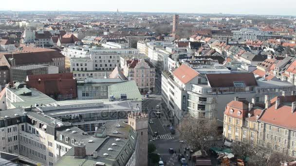 München mit seiner Rindermarktstraße. Autos fahren die Straße entlang. Ein schnell heranfahrendes Polizeiauto. Luftaufnahme von der Peterskirche.
