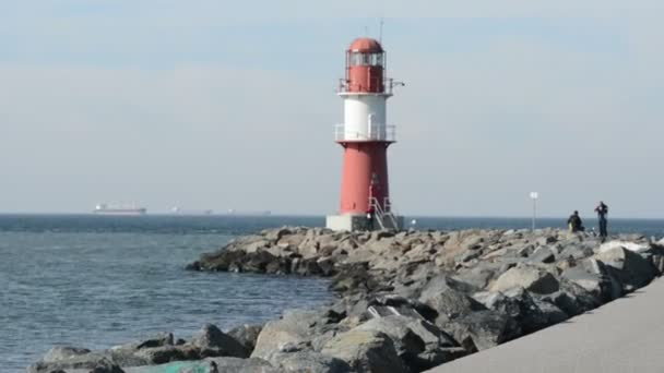 Group of people is visit the red lighthouse of Warnemuende at Baltic Sea. Its the entrance of harbor.