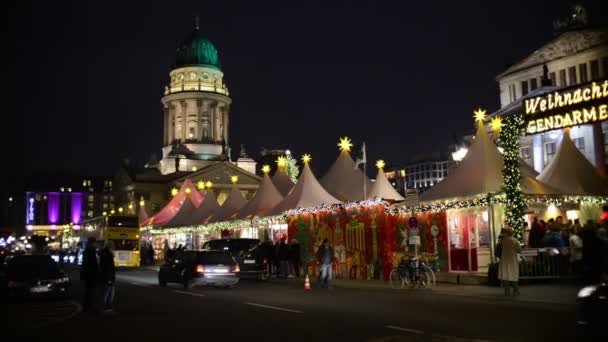 people walking around on the place of christmas market in berlin gendarmenmarkt. in background the concert house and german cathedral. in front cars passing by
