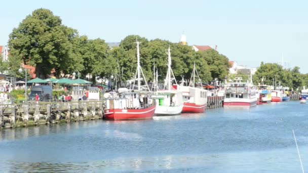 People visiting harbor with boats and stores. (Warnemuende)