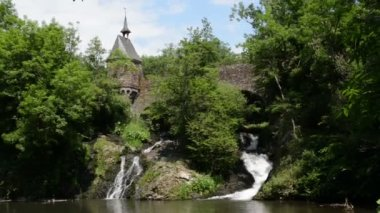 Waterfall of Elz river with small church on a bridge and an old half timbered watermill. The river flows along the village Monreal and the castle Burg Eltz. (Eifel, Germany)