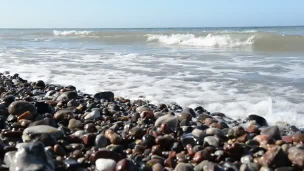 Hullámok a parton a Balti-tenger strandon (Mecklenburg-Vorpommern, Németország). A jobb oldali tipikus homokdűnék.