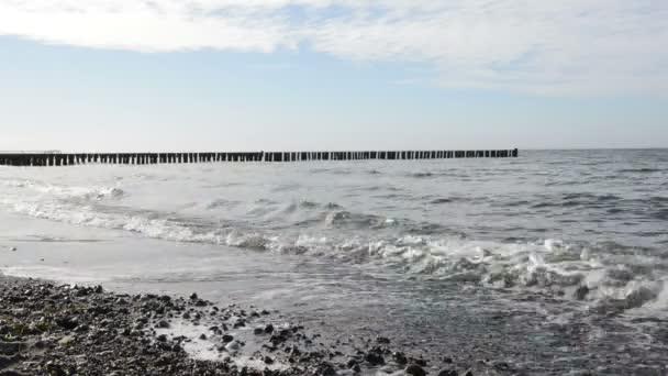 Prolomit vlny na pobřeží s oblázky