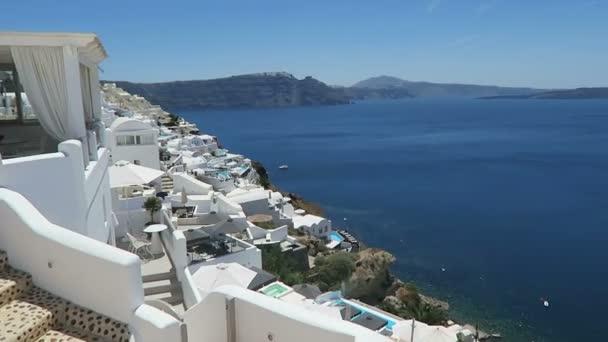 Cityscape of Ia, town at Santorini Isle (Greece). people walking along the promenade.