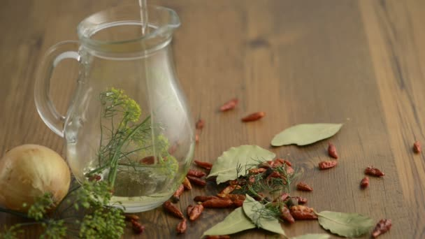A carafe is filled with oil. Therein lie herbs such as dill and chili peppers. Outside are around other spices such as bay leaves, onion, chili