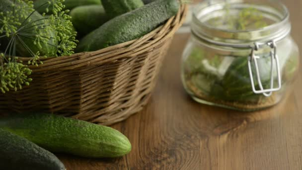 Spices like dill, chili, mustard seeds falling into a canning jar on a table. Aside a basket with green cucumbers