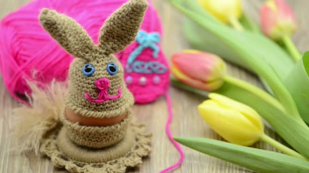 Crochet Easter bunny egg cup made of wool. fresh tulips and wool ball in background