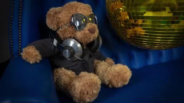 barna maci bolyhos játék napszemüveg és fejhallgató disco labda kanapén háttér