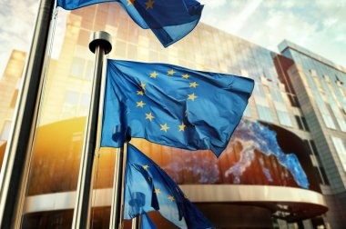 EU flags waving in front of European Parliament building.