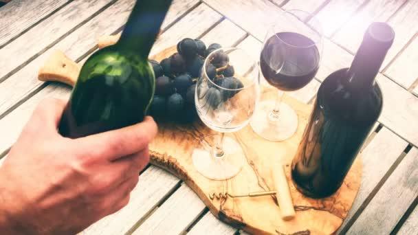 Muž, nalil do sklenice na víno červené víno z láhve. Ochutnávka vín koncept. Venkovní romantická večeře pozadí