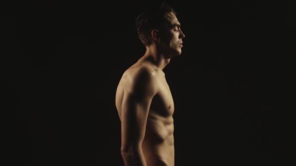 sexy Sport entblößter Kerl in Wassertropfen mit Rauch auf isoliertem schwarzem Hintergrund