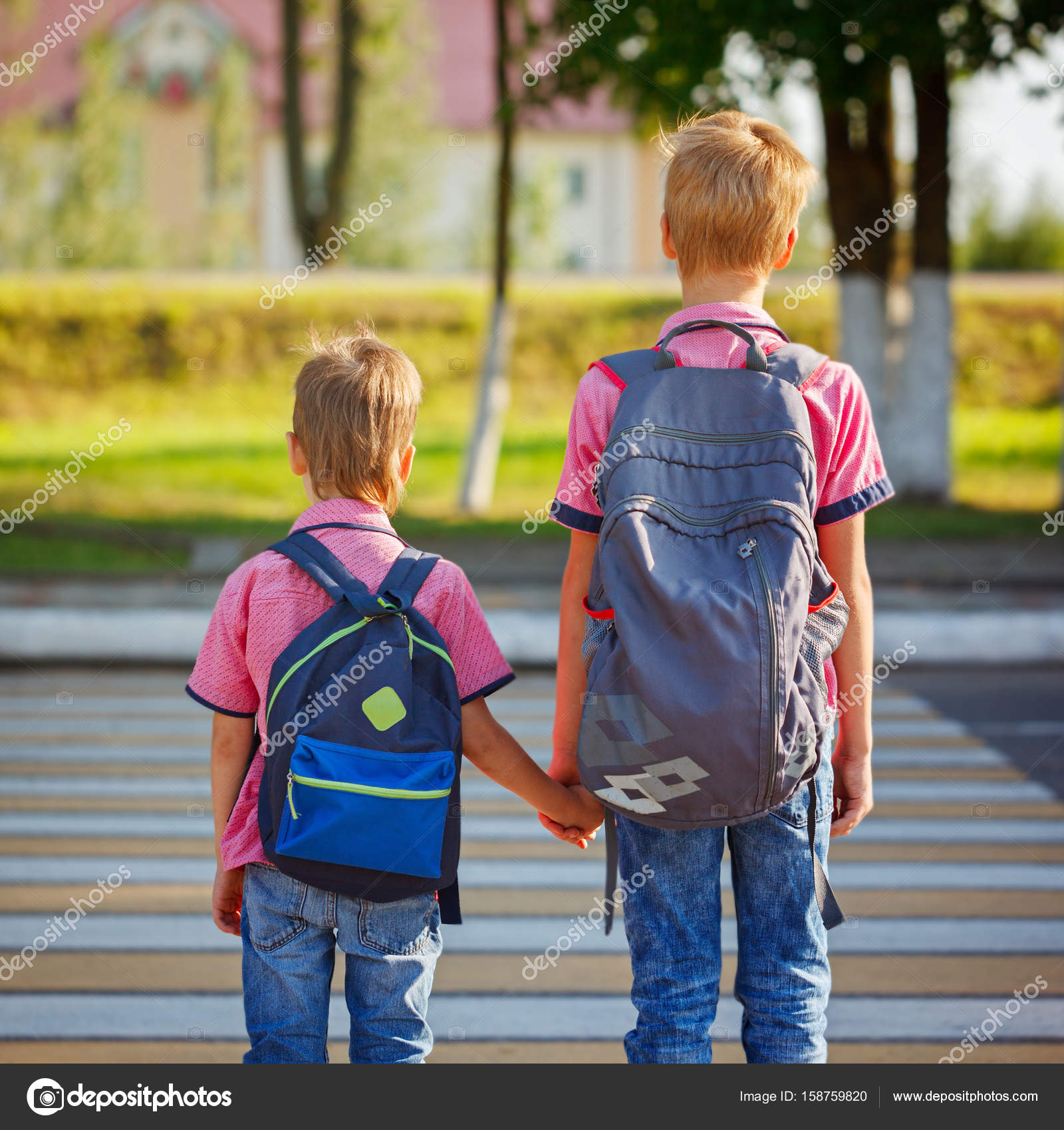 Two Kids With Backpacks Walking On The Road Holding School Time