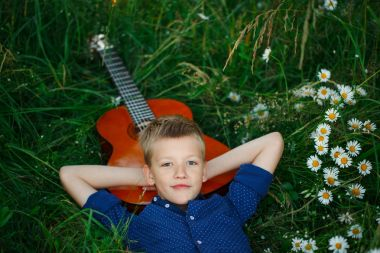 Portrait Teenage boy lying on grass with his acoustic guitar.