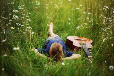 Teenage boy lying on grass with his acoustic guitar