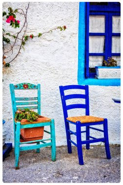Typical cute wooden chairs in street taverna in Greece. artistic picture.