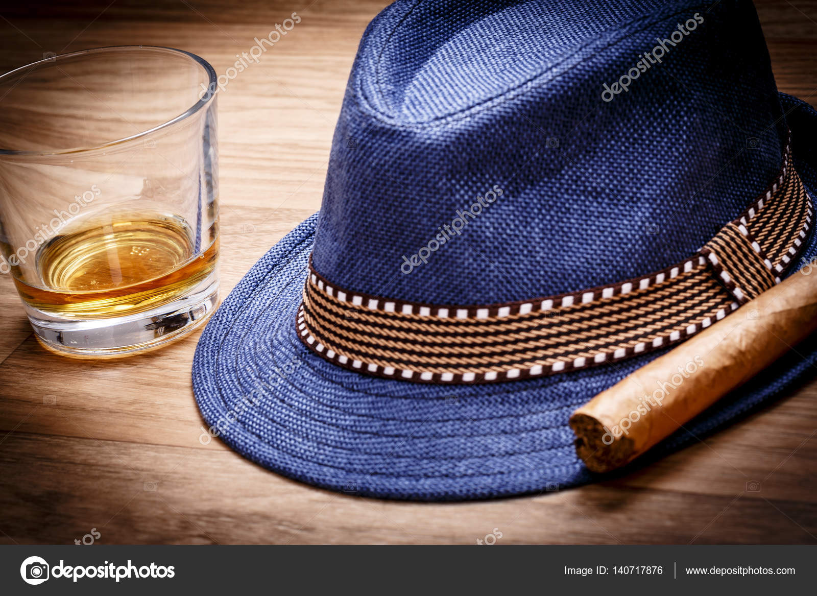 7615fc9444061 Blue hat with cigar and expensive drink of whisky or rum on wooden floor–  stock image