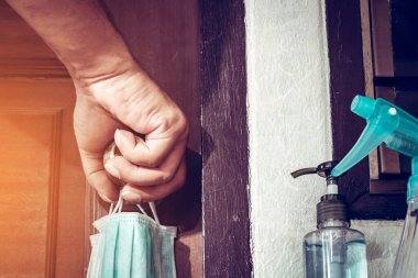 Two masks for lovers hanging on the bedroom door knob with alcohol gel to wash hands to prevent prevent the spread of germs and avoid infections corona virus (Covid-19)