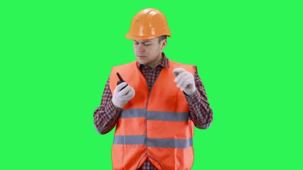 Man in a construction helmet and orange vest is talking on the walkie-talkie, green screen background