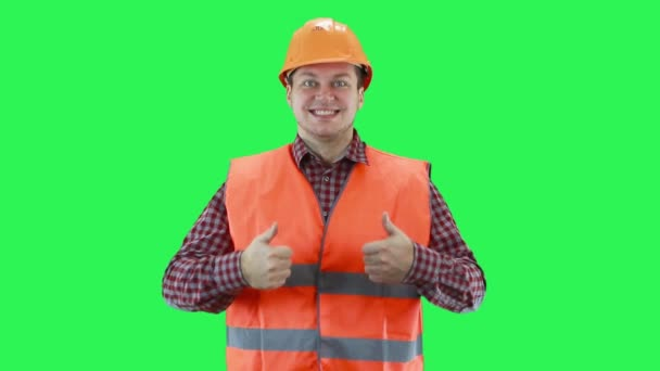 Man in a construction helmet and orange vest shows with his hands that everything is fine, green screen background