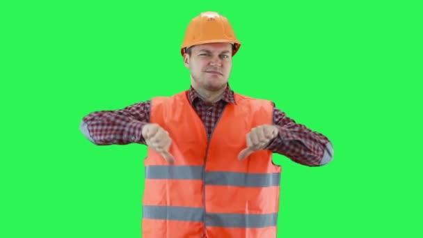 Muž ve stavební helmě a oranžové vestě ukazuje s rukama, že všechno je špatné, zelená obrazovka pozadí