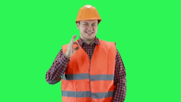 Man in a construction helmet and orange vest hand shows ok, green screen background
