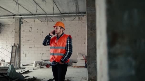 Stavitel v oranžové vestě mluví po telefonu na pozadí staveniště.