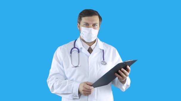 Ein medizinischer Mitarbeiter hält Dokumente zum Schreiben in der Hand.
