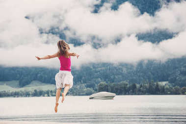 Woman jumping at the lake